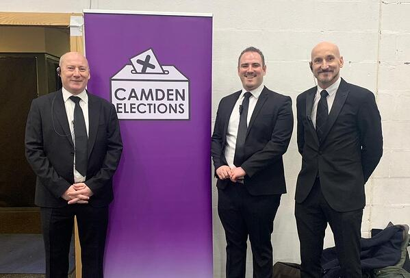 Off to Work's Head of Security, Jason Henderson, standing between two security personnel at the Camden Elections in December 2019